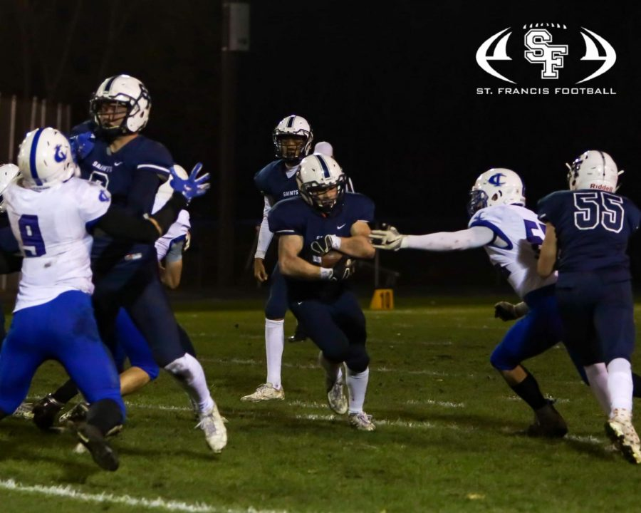 The+Saints%27+Jordan+Haller+carries+the+ball+low+and+tough+in+the+first+playoff+game+against+Cambridge-Isanti.+The+Saints+won+37-7.