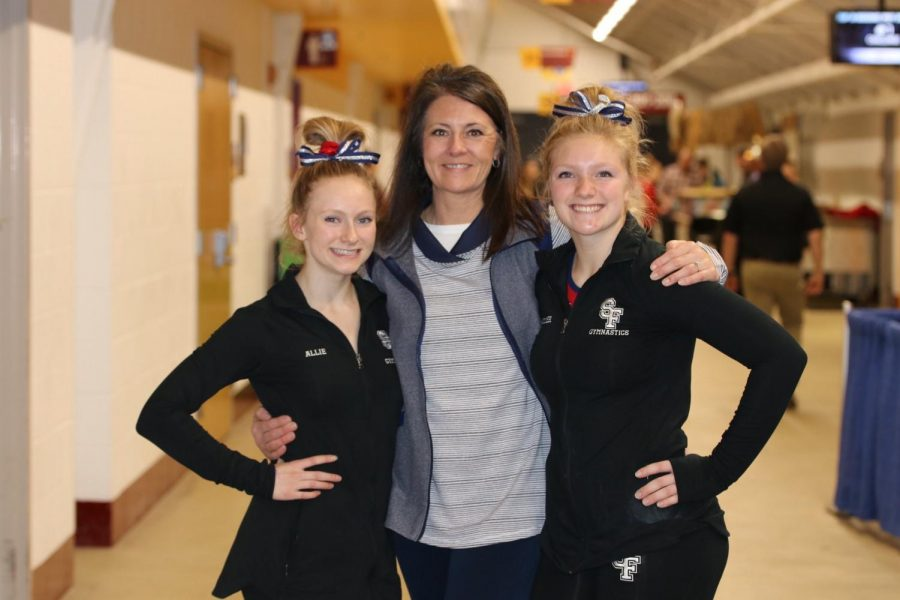 Girls gymnasts pose with their coach before heading off to state competition.